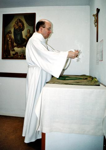 The priest prepares to celebrate the Eucharist. He wears a white alb and girdle (belt), a green chasuble and stole (scarf). The chasuble and stole are green – this shows that the church is in ordinary time in the church year.